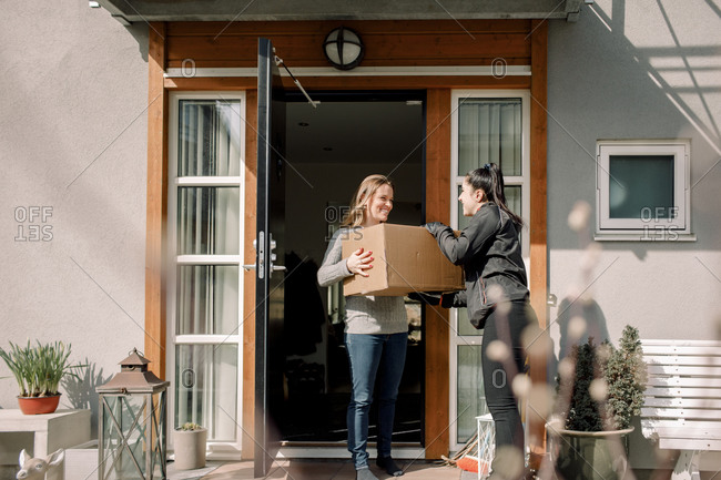Female customer receiving box from young delivery woman