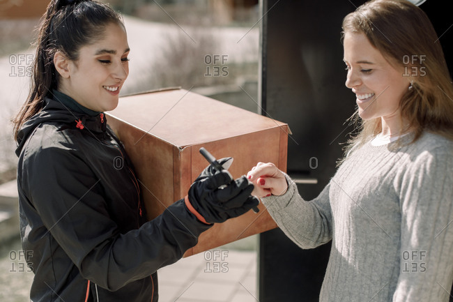 Female customer signing on smart phone while receiving package from delivery woman