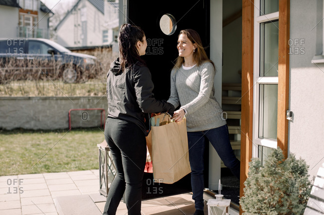 Female customer receiving package from delivery woman