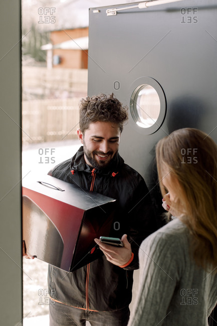 Female customer receiving package from delivery man