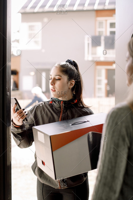 Delivery young woman using mobile phone while delivering package to customer