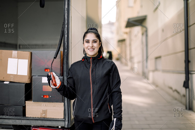 Portrait of confident young delivery woman with truck on in city