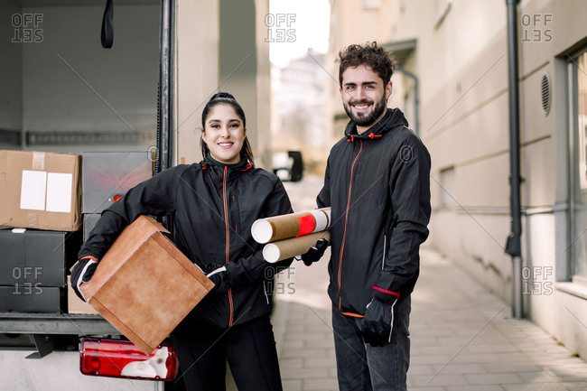 Portrait of confident delivery man and woman with packages standing against truck in city