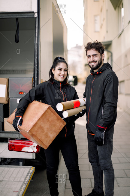Portrait of confident young delivery man and woman with packages standing against truck in city