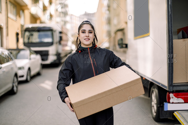 Portrait of young delivery woman carrying box while standing on street in city