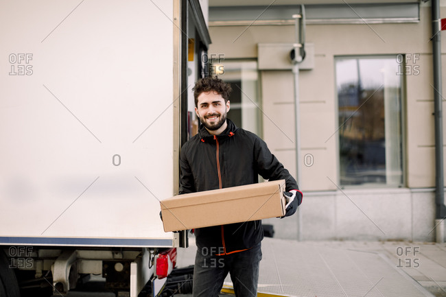 Portrait of confident young delivery man with box leaning on truck