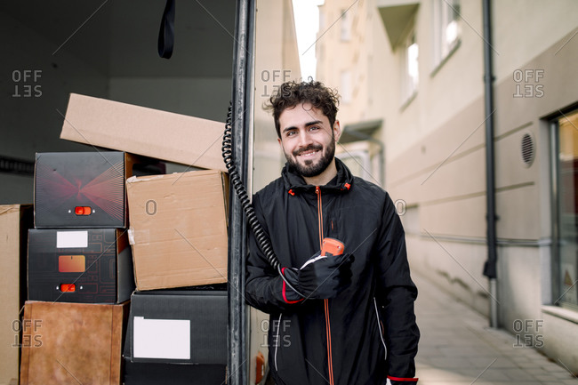 Portrait of confident delivery man with boxes in truck