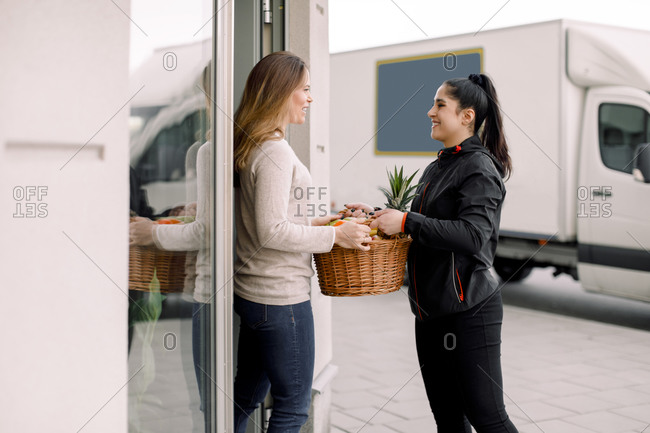 Delivery woman delivering fruits to mature female customer