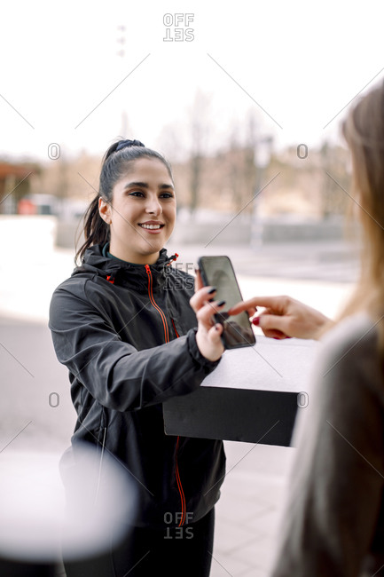 Customer signing on smart phone while receiving package from delivery woman