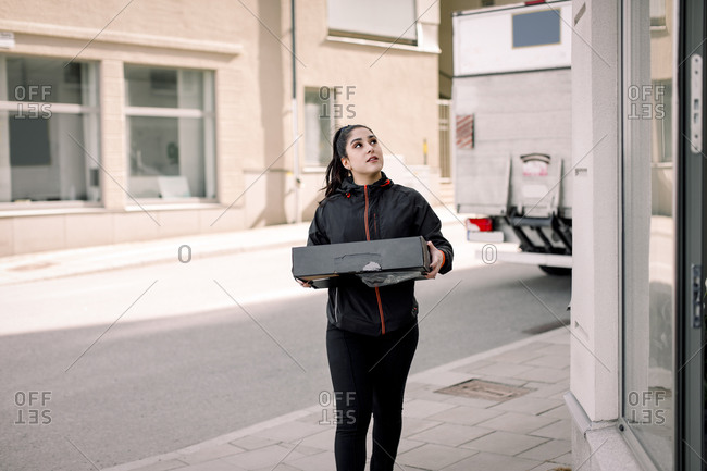 Young delivery woman delivering package at building