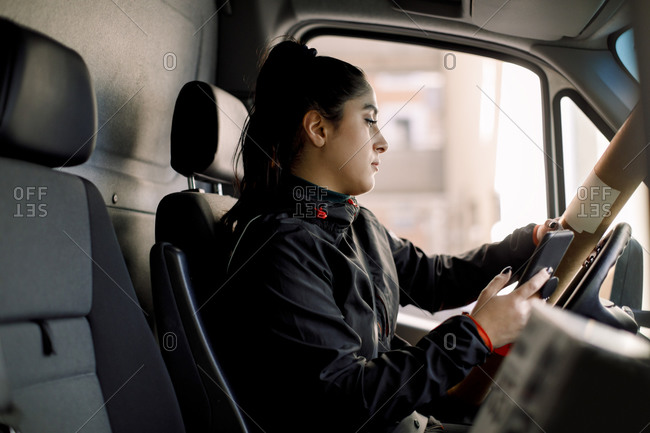 Delivery woman with package using smart phone while driving truck