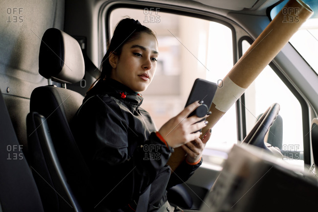 Young delivery woman using smart phone while holding package in truck