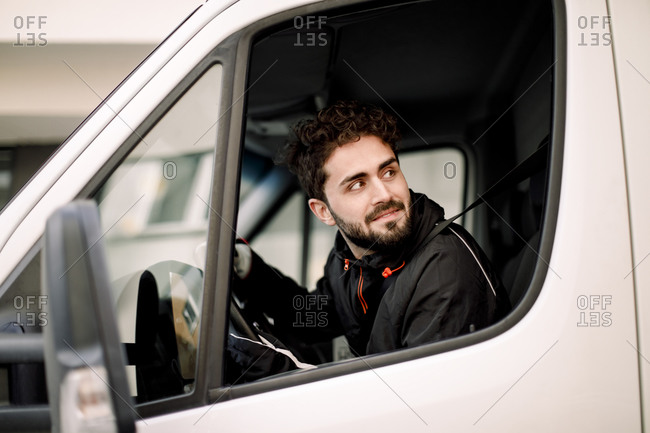 Young delivery man looking through window while driving truck