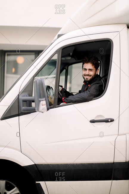 Portrait of smiling young delivery man driving truck