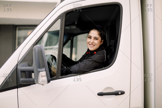 Confident young delivery woman driving truck