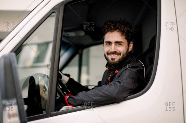 Side view portrait of confident young delivery man driving truck