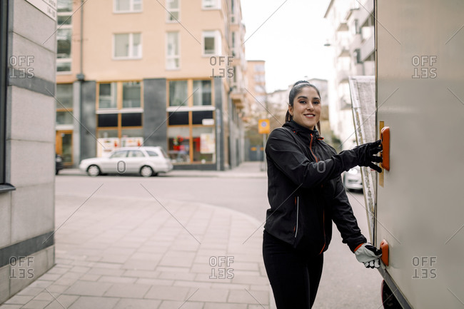 Portrait of confident young delivery woman with truck in city