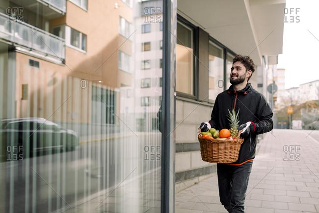 Young man delivering fruit basket in building