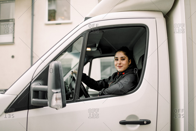 Portrait of young delivery woman driving truck