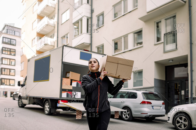 Young delivery woman carrying box on street