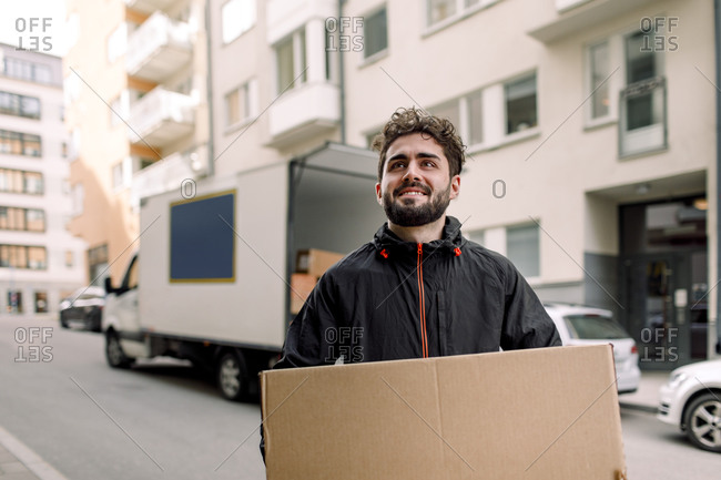 Confident young delivery man carrying cardboard box in city