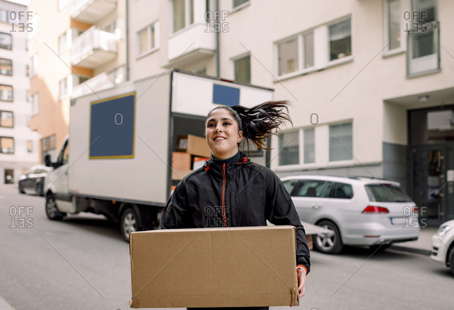 Confident young delivery woman carrying cardboard box on street in city