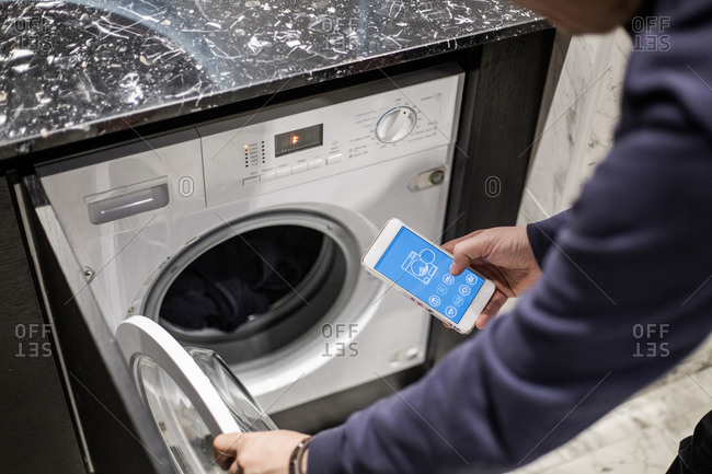 Cropped image of man controlling washing machine with mobile app at smart home