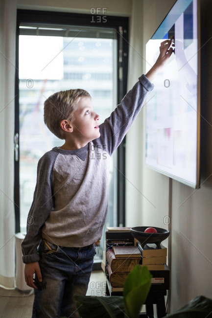 Boy touching digital display of smart television set at modern home