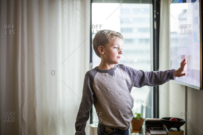 Boy touching screen of smart TV at modern home
