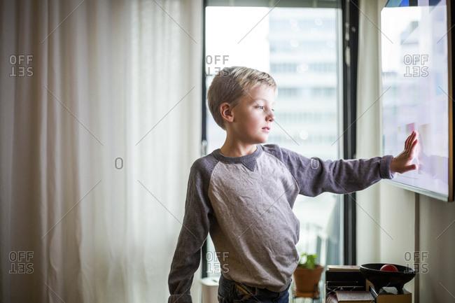 Boy touching screen of smart TV at modern home
