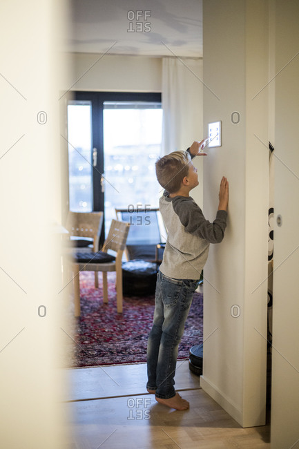 Full length of boy using digital tablet mounted on wall at modern home