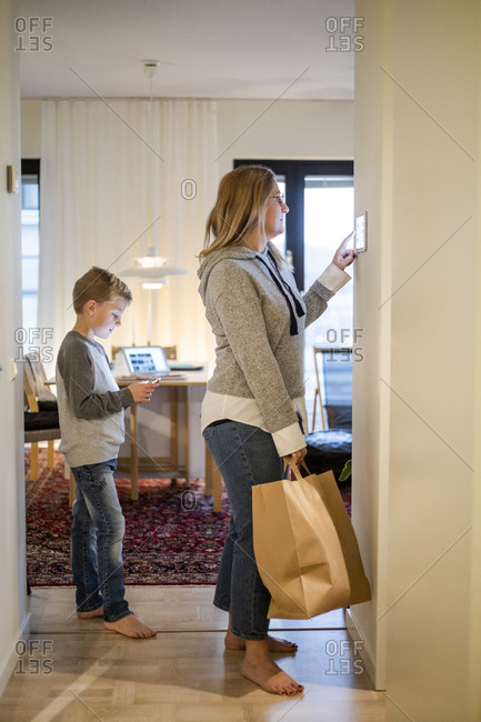 Mother with shopping bag using digital tablet on wall while son standing at home