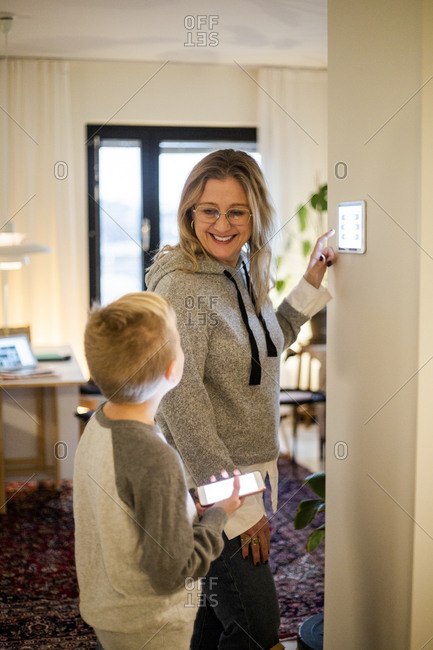Smiling mother talking to son while using digital tablet mounted on wall at smart home