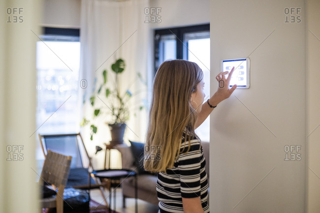 Girl using digital tablet mounted on wall at modern home