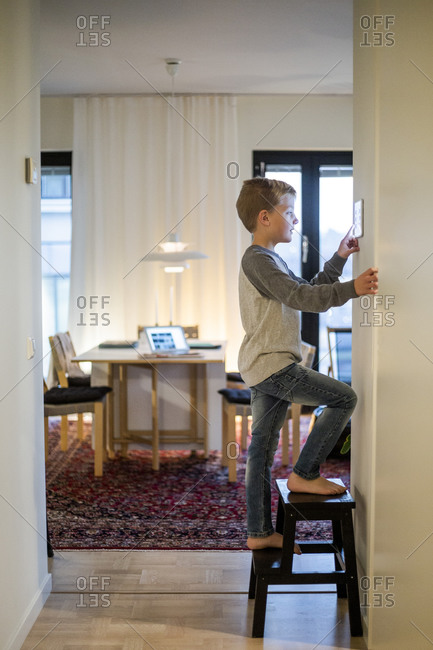 Boy standing on stool while using digital tablet mounted on wall at smart home