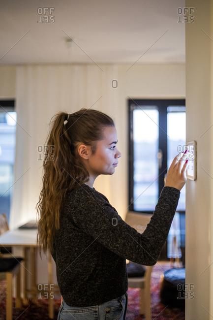 Teenage girl using digital tablet mounted on wall in smart home