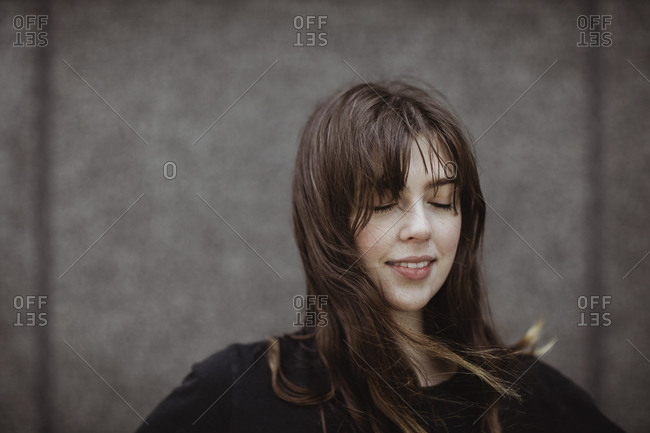 Smiling woman with eyes closed standing outdoors