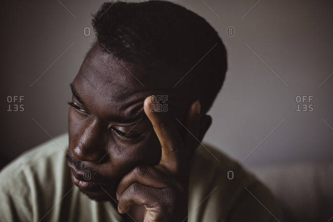 Close-up of sad man holding head in hand while looking away