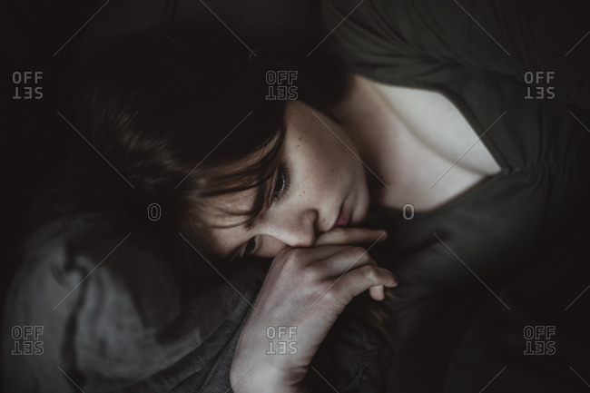 Close-up of sad woman lying on bed