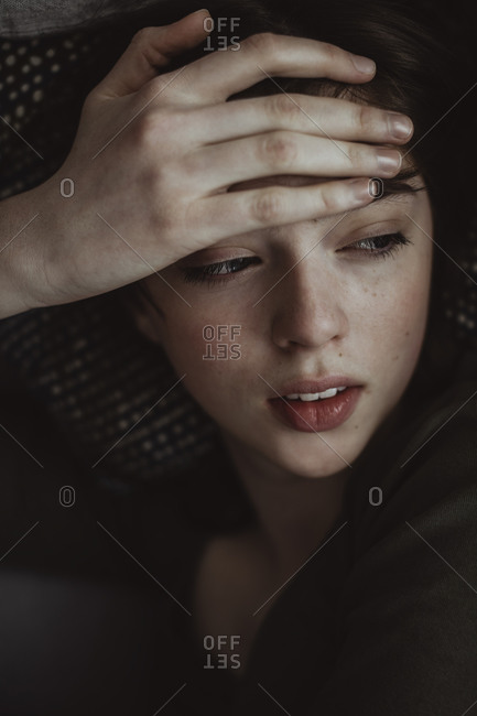 Close-up of woman with headache looking away while lying on sofa