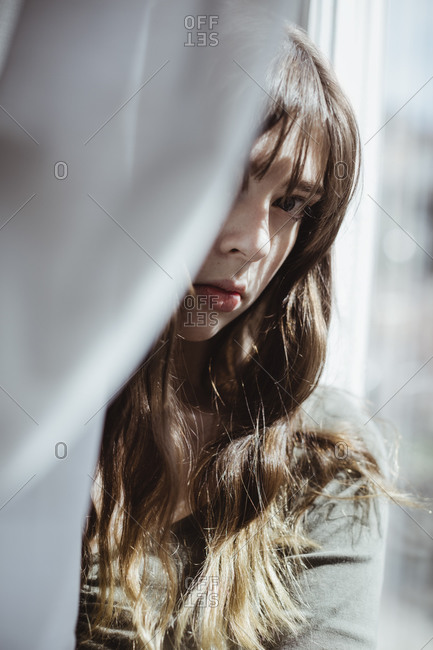 Portrait of woman hiding behind window curtain