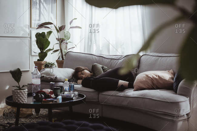 Worried young woman lying on sofa at home