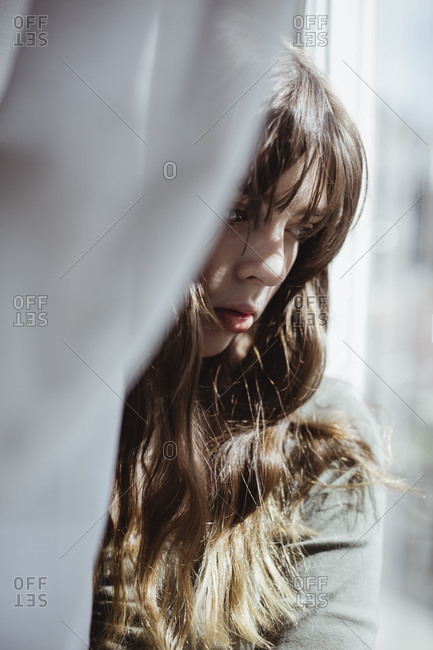 Close-up of young woman hiding behind window curtain