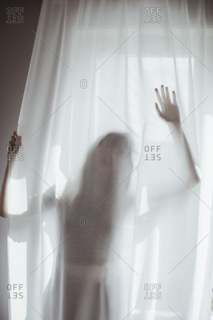 Young woman hiding behind white curtain