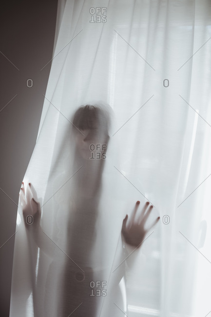 Young woman hiding behind curtain