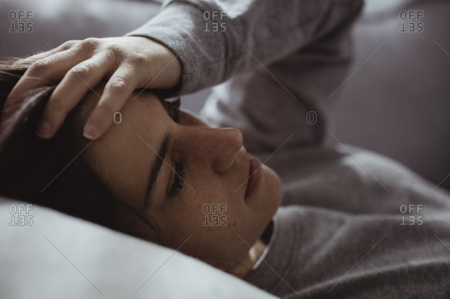 Close-up of worried woman lying on sofa at home