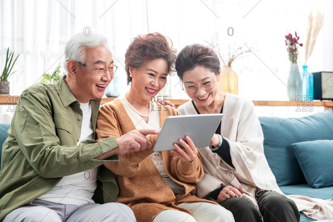 Happy elderly people watching a show on a tablet