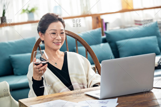 Middle-aged woman using laptop at home while drinking wine