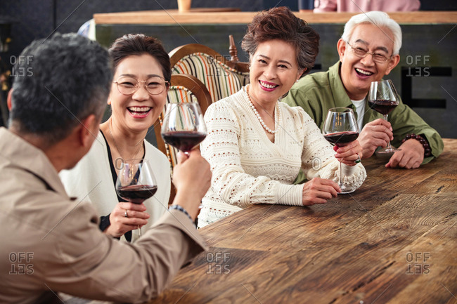 Middle-aged friends drinking wine together