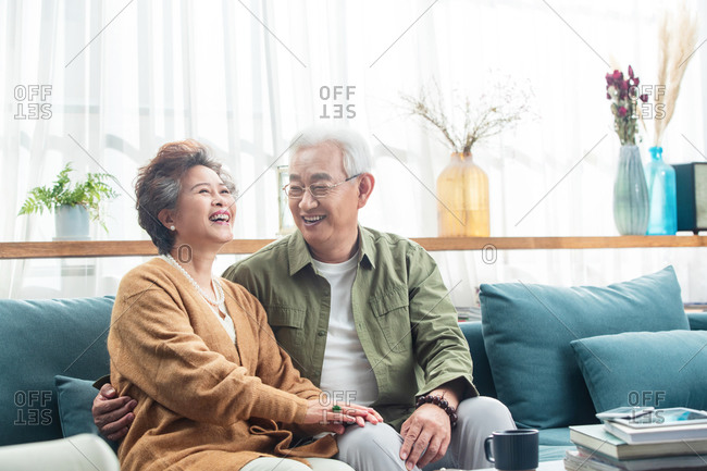 Elderly couple happily talking together on the sofa